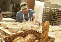 John Reichert, head baker and one of the three 'Crumb Brothers,' shaping bread dough at Crumb Brothers Bakery in Logan