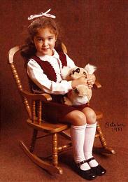 Lori Soares holds a stuffed animal in a portrait taken as a little girl